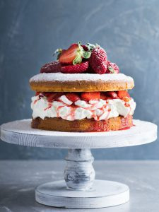 British Victoria sponge cake with berries on a cake pedestal