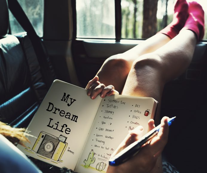 a woman sitting in a car with her feet resting on the opened window as she writes in her journal that has a photo of a camera with the words, My Dream Life