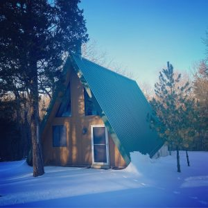 an A-frame cabin in the snowy woods