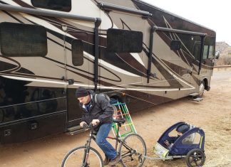 a dad on a bike pulling his son behind him next to an RV