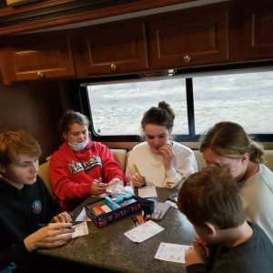kids sitting around a table in an RV playing board games