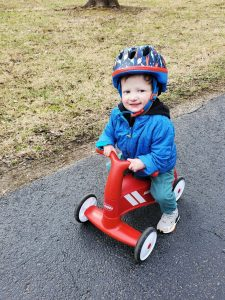 a little boy with Rothmund-Thomson Syndrome, wearing a helmet and riding on a red scooter bike