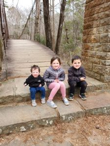 a little boy with a rare disease, Rothmund-Thomson Syndrome, sitting on a bridge next to his sister and brother