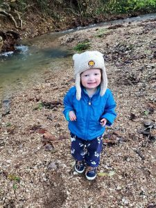 a toddler with a blue coat and white hat near a river