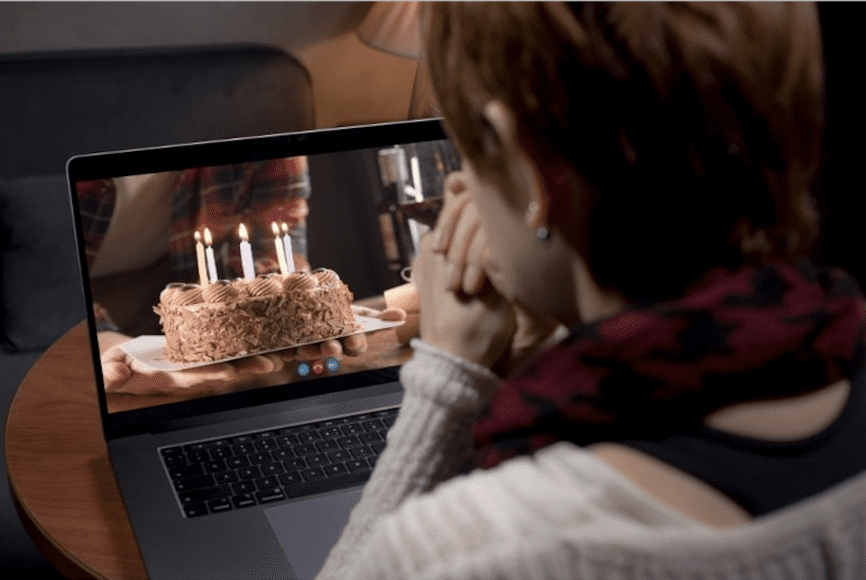 a view of a woman from behind as she is presented a cake on the computer, symbolizing a virtual birthday
