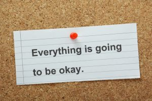 """a white notecard that says, """"Everything is going to be okay"""" pinned to a cork board with a red tack."""