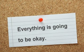 "a white notecard that says, ""Everything is going to be okay"" pinned to a cork board with a red tack."