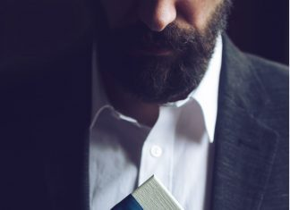 a man with a beard, wearing a suit and opening a gift with a blue ribbon
