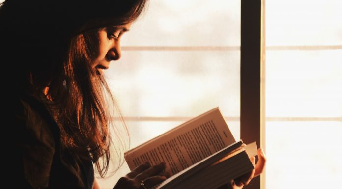 a woman sitting by a window reading a book