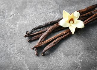 a cluster of vanilla beans with a vanilla flower on top on a marble tabletop