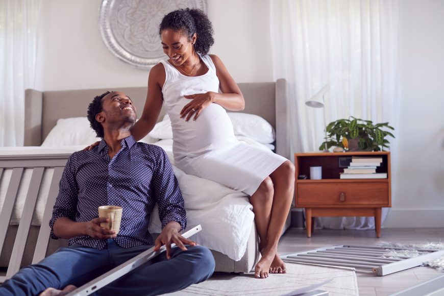 an African American couple setting up a crib in the master bedroom