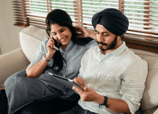 a couple sitting on the couch, him with a tablet and her with a phone, as they join a virtual celebration