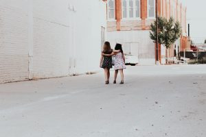 two girls, walking down a street with their arms around each other