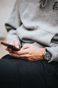 partially visible person texting on phone