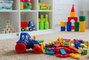 toys on the floor in a playroom with shelves of toys in the background
