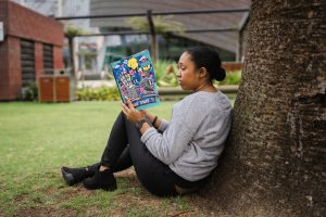 a young adult leaning against a tree as she reads a book about women's history month