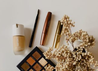 clean skincare and beauty products such as a pallet of brown eyeshadow, mascara, and foundation, on a cream colored background with flowers