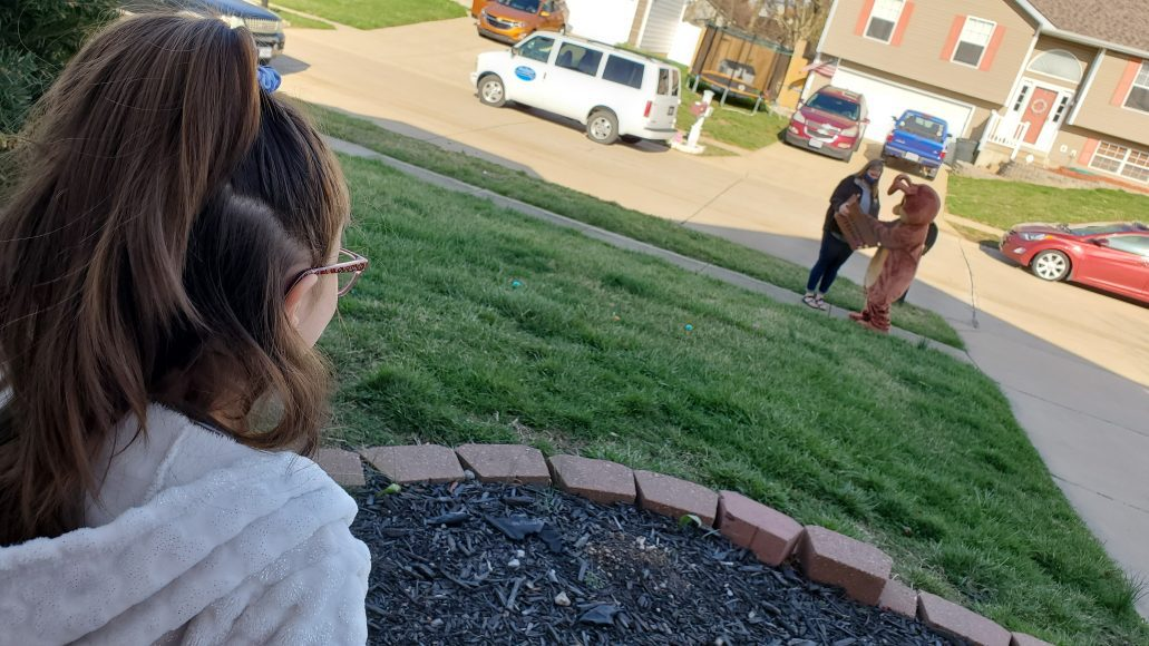 little girl watches Easter Bunny delivery from porch