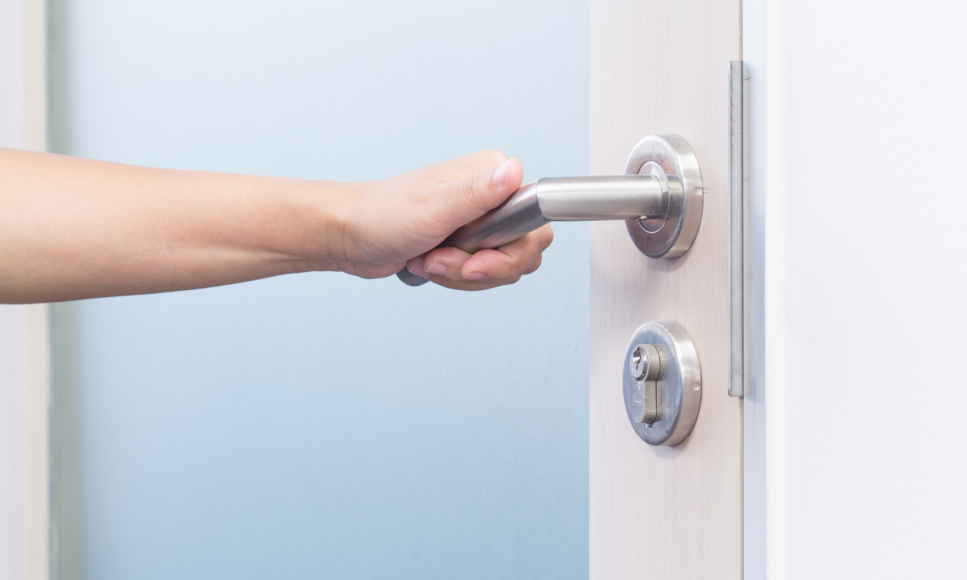 a close up of a hand reaching for the handle of a closet door to open it