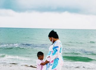 a mom and her son standing at the shore as a photo is taken