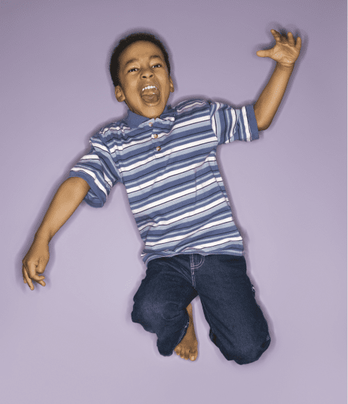 an African American boy in a striped shirt and jeans jumping up into the air as he yells