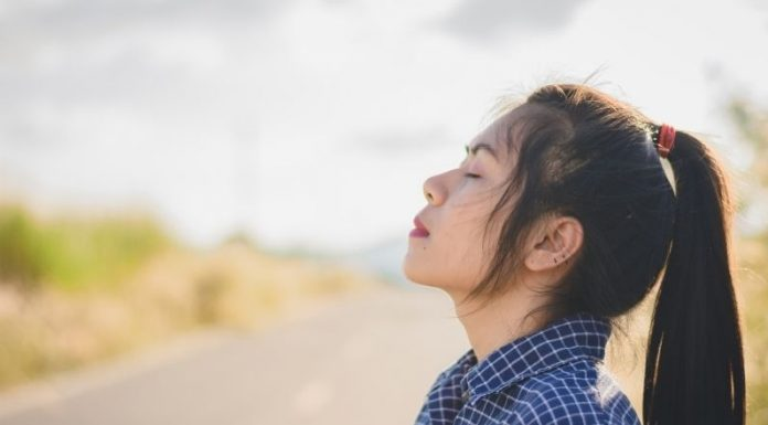 a woman standing at the side of the road with her eyes closed, taking a deep breath