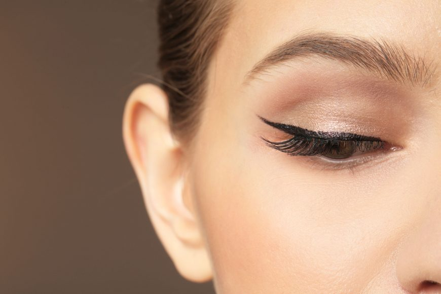 a close up of a woman with winged eyeliner make up