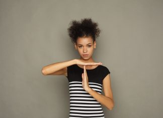 """an African American woman in a black and white striped dress holding up her hands in the """"timeout"""" signal"""
