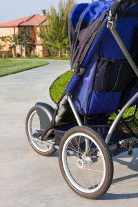a blue jogging stroller from behind on a sidewalk meandering through a neighborhood