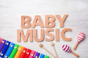 """wooden letters that spell """"baby music"""" next two a xylophone and maracas"""