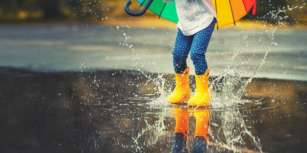 a child in yellow rain boots splashing in puddles as she carries a rainbow umbrella