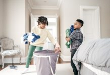 two kids putting laundry from the basket away
