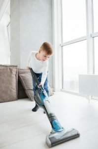 a boy vacuuming the floor with a stick vacuum