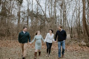 surrogacy: a pregnant couple walking through the woods with the couple whose baby they are carrying