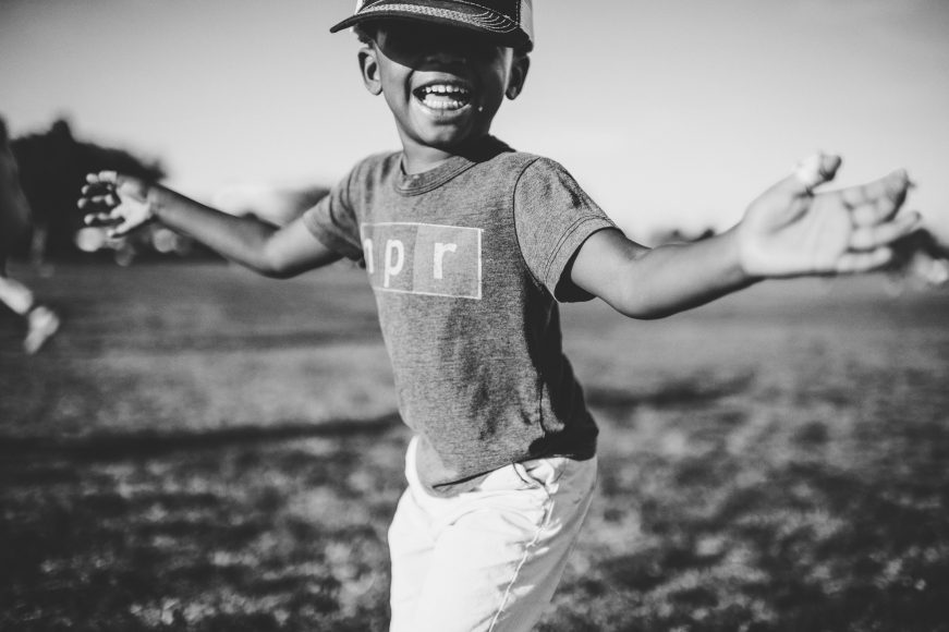 a black and white photo of an African American boy standing in a garden, with his arms outstretched and a smile on his face