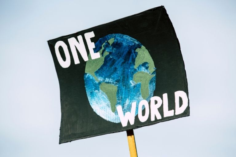 """a black sign with the earth on it that says, """"one world"""" held up high against the sky"""