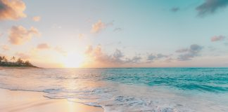 turquoise water lapping on the shoreline as the sun rises in the distance