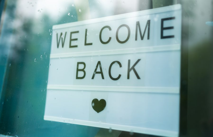 """a sign in a window saying, """"welcome back"""" with a heart underneath"""