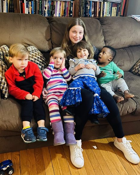 four toddlers and a teenager squeezed together on a couch