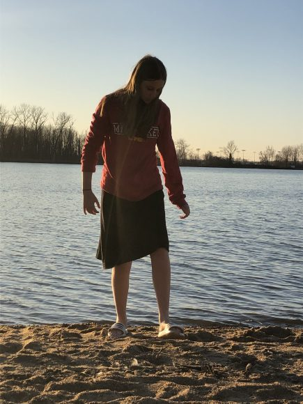 a girl walking barefoot up the sand, away from Creve Coeur Lake in Saint Louis