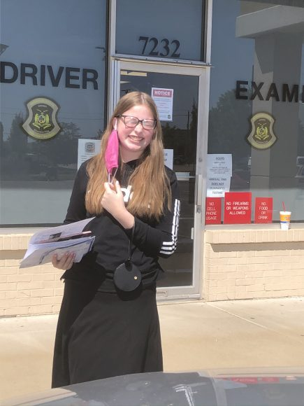 a teen girl standing outside of the driver's exam office holding her new drivers license