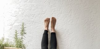 a woman laying on the floor with her feet up against the wall to relax and handle stress