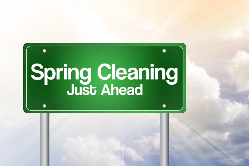 a green road sign that says Spring Cleaning Just Ahead