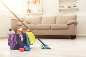 a bucket of cleaning supplies with a mop leaning against it in front of a beige couch
