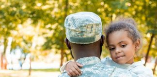 a close up of a military dad from behind as he holds his daughter, whose face we see is smiling