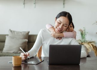 a woman sitting at a desk in front of her open laptop, pen in hand as her toddler daughter wraps her arms around her mom's neck from behind