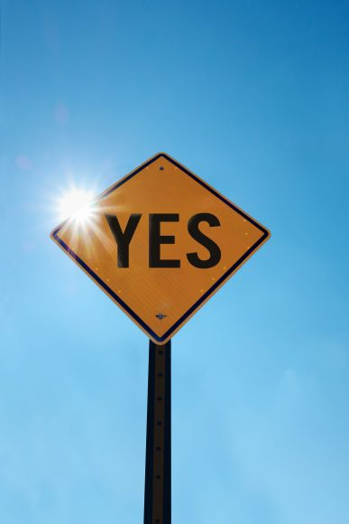 a yellow diamond street sign with the word YES written in black, set against a blue sky
