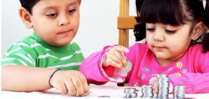 a boy and a girl stacking up coins as they count their money