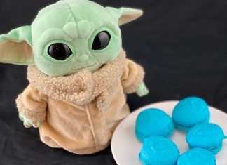 a baby Yoda stuffed toy next to a plate of blue macarons in honor of May the Fourth