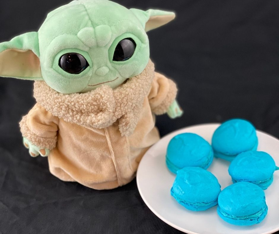 a Star Wars stuffed toy next to a plate of blue macarons in honor of May the Fourth